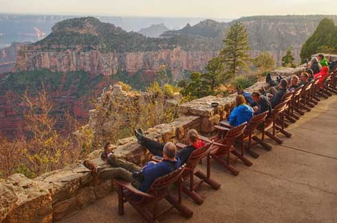 about one dozen people sitting in wooden deck chairs and looking over the stone patio wall at Grand Canyon during sunset.