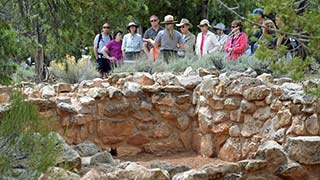 In the foreground, the partial ruin wall, about three feet high. In the background, a ranger has her back to the camera and is addressing a group of 10 people who are taking her tour.