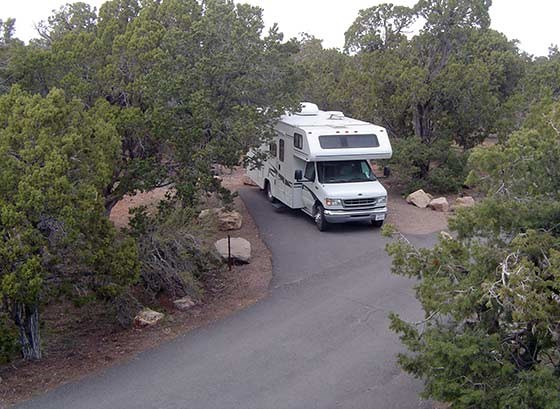 Looking down through trees at a white recreational vehicle parked in a family site at the Desert View Campground.