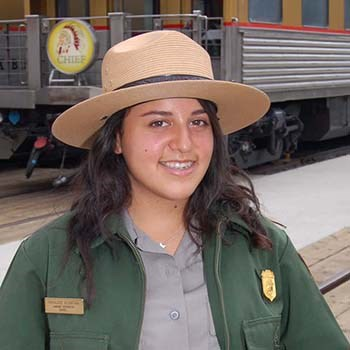 A female ranger in uniform standing in front of a passenger train car.