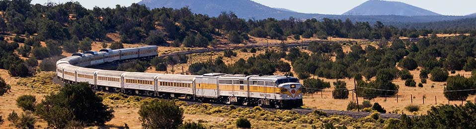 Diesel locomotive pulling 10 passenger cars around a curve to the right through pinyon-juniper woodlands south of Grand Canyon
