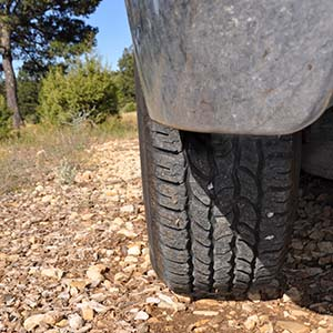 rear view of an off-road jeep tour tire on a dirt road.