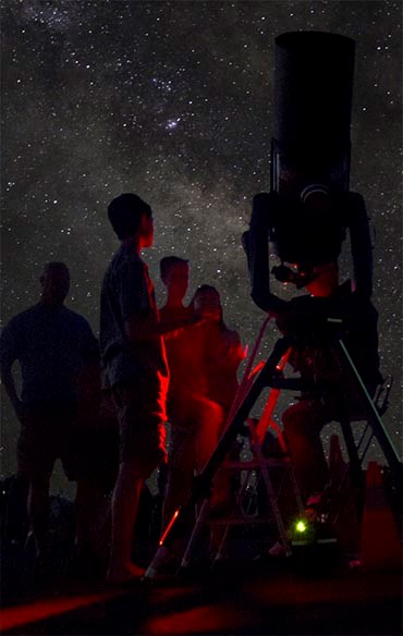 a starry night. a family is gathered around a large telescope as an astronomer is talking. Everyone is bathed in red light.