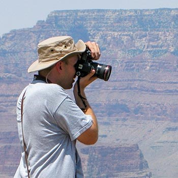 A person wearing a floppy sun hat is photographing outdoors with canyon walls in the background.