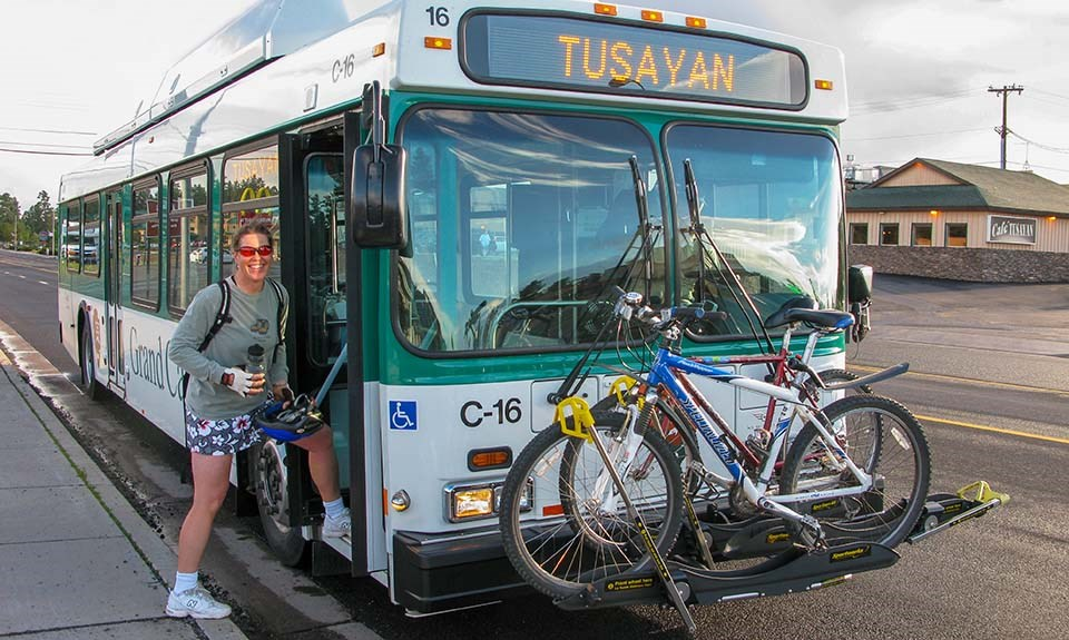 a woman boarding a white and green bus with a rack with two bicycles in front.