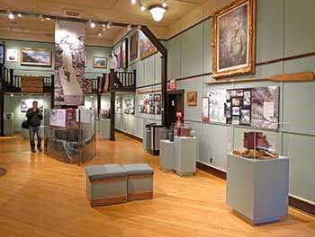 Exhibit hall with two-story ceiling and a wooden floor. Paintings and exhibits hanging on the sage green walls. Several stand-alone cases with antique cameras.