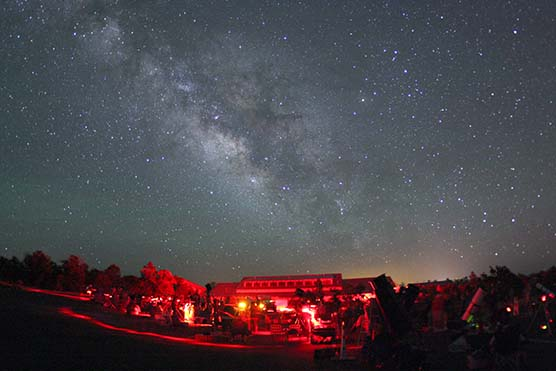 Telescope lot at Grand Canyon Star Party bathed in red light. The Milky Way is seen overhead stretching across the sky.