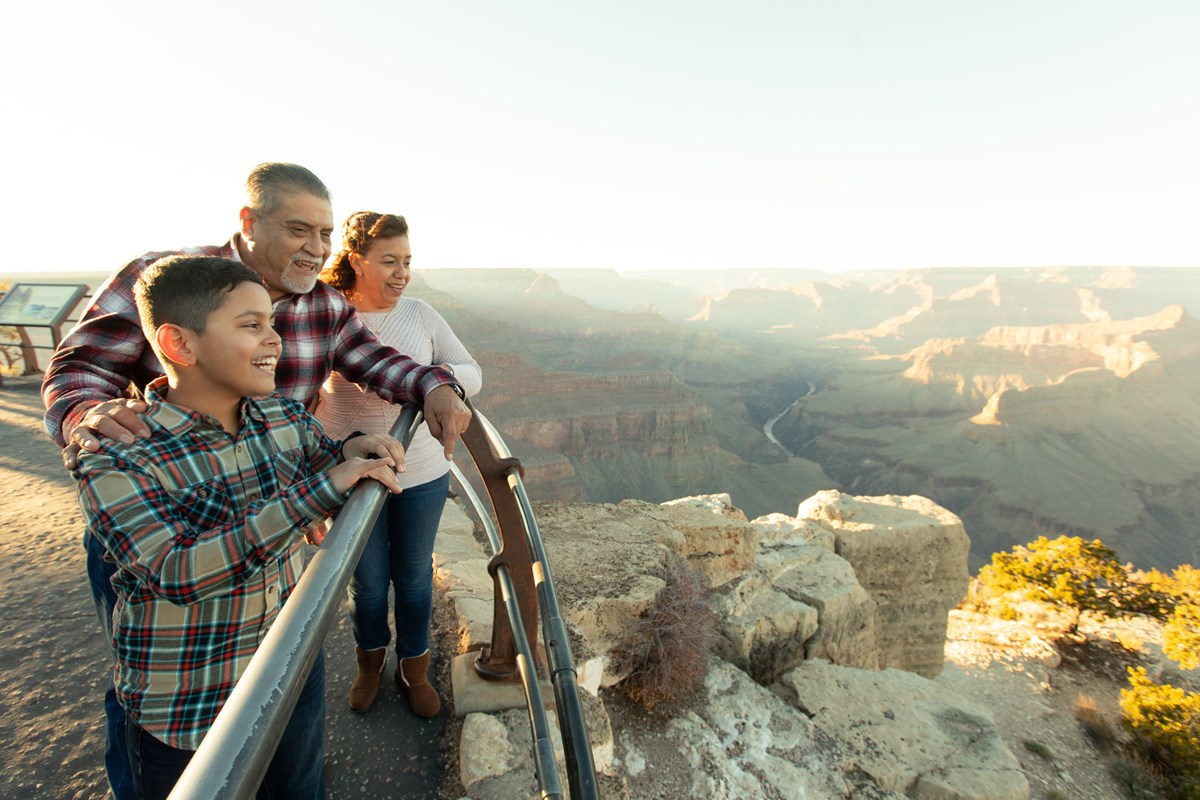 A family viewing the Grand Canyon safely from behind the railing at an overlook.