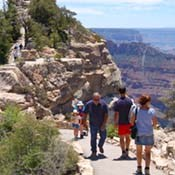 Several day hikers on the paved footpath to Bright Angel Point, North Rim Grand Canyon visible in the distance on the right.