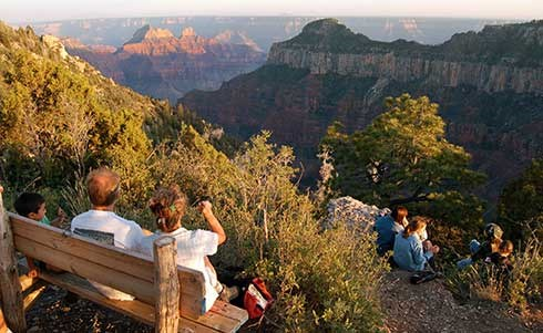 A group of people watching sunset from an overlook at the south end of the campground. Several are sitting on a bench on the left. Others are sitting on a ledge below and to the right.