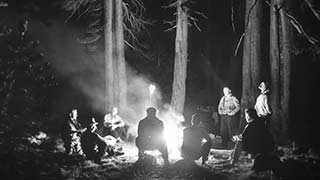 black and white photo of a group of people gathered around a campfire under tall pine trees.