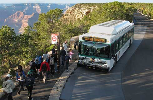 Shuttle bus passengers boarding at Hermits Rest. Grand Canyon beyond.