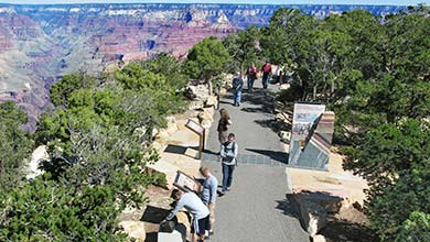 Visitors walking along the Trail of Time path on the rim of Grand Canyon