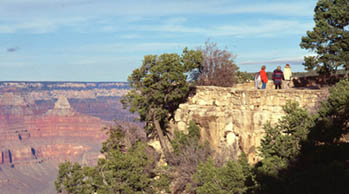 Several people are walking along the canyon rim behind a stone guard wall. The canyon is visible on the left