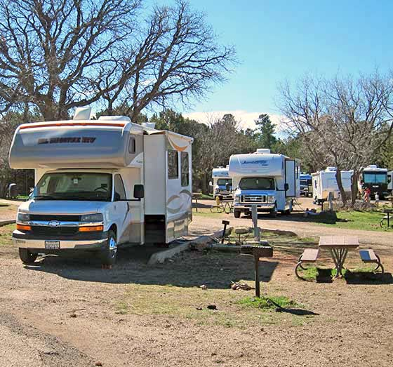 RV parked in Trailer Village site with full hook-ups showing grill and picnic table.