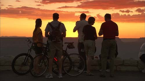 Two bicyclists along with several other people in silhouette are watching sunset at Grand Canyon