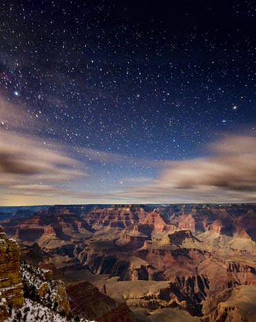 Moonlight illuminating the Grand Canyon landscape. Between clouds above, stars are visible.