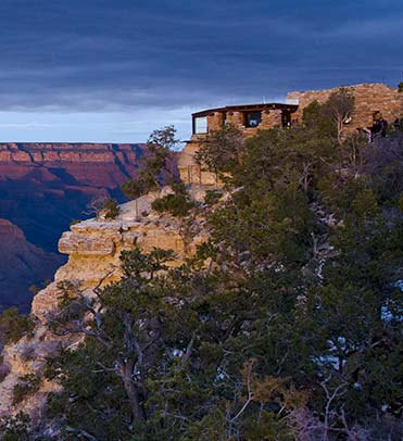 Looking over trees as the ast rays of pinkish sunset falling on rustic stone Geology Museum on the edge of Grand Canyon - seen in the distance