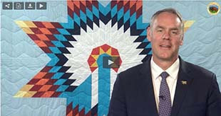 Secretary of the Interior Zinke wearing a blue suit and tie, is standing in front of a quilt decorated with an American Indian design.