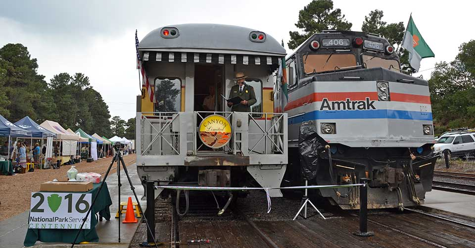 "Two trains parked at the Grand Canyon Depot with tents on the left side. In bottom left is a sign reading ""2016 National Park Service Centennial."""