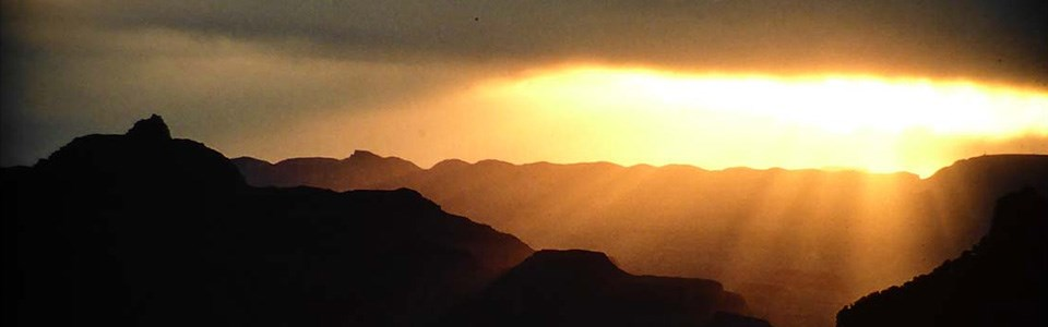 The sun comes up above the canyon at sunrise.