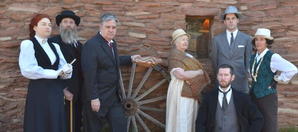 Wearing turn of the 19th Century clothing, 7 members of the Echoes From the Canyon living history production are posing in front of an adobe wall. A large wooden wagon wheel is in the center of the photo.