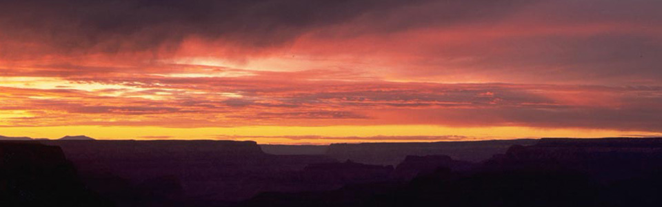 Pink and orange skies over the canyon during sunset.