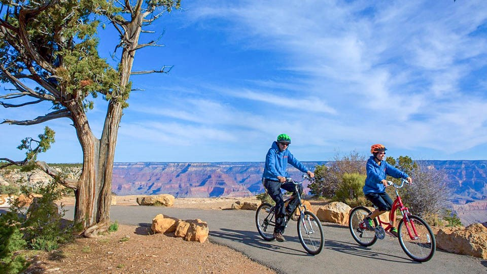 Image: 2 bicyclists riding along a paved greenway path along the edge of a colorful canyon landscape