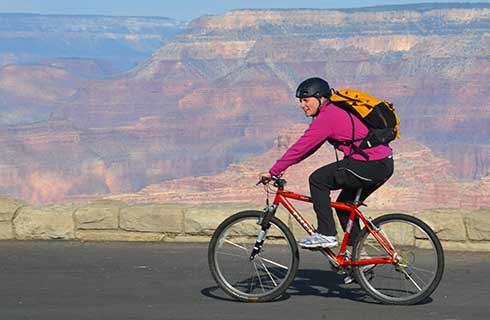 Smiling woman riding a red bicycle along Hermit Road. Grand Canyon beyond.
