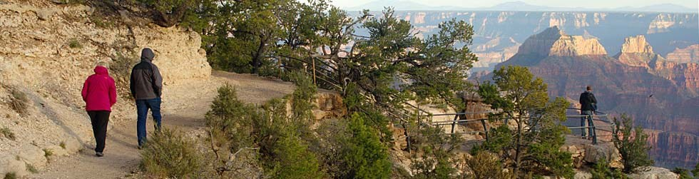 two people walking on a trail. a scenic overlook is on their right with Grand Canyon in the distance