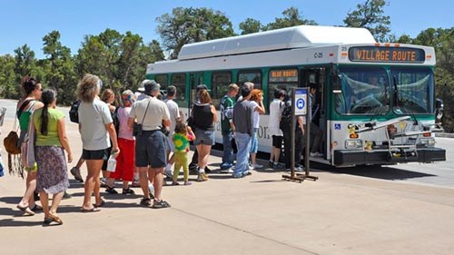 a line of people boarding a green and white bus.