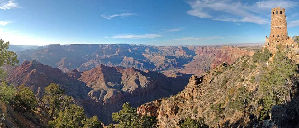 An expansive view of Grand Canyon from Desert View with the Watchtower in the upper left, perched on the edge of a cliff