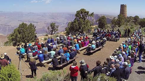 Around 100 people gathered for the rededication of Desert View Watchtower. The audience, seated on benches in the foreground are near the edge of Grand Canyon. the Watchtower is seen off in the distance.