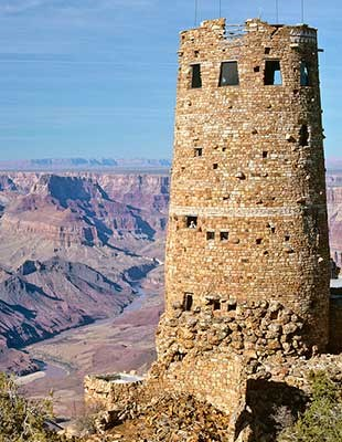 On the edge of a canyon, a cylindrical stone tower, four stories high. In the distance a river flows between purple slopes and cliffs.