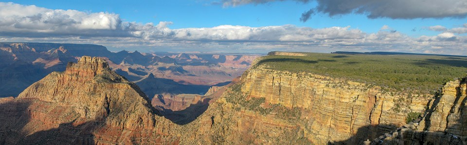 Rising from the floor of a vast canyon, a rugged peak that is connected to the canyon's rim by a v-shaped saddle.