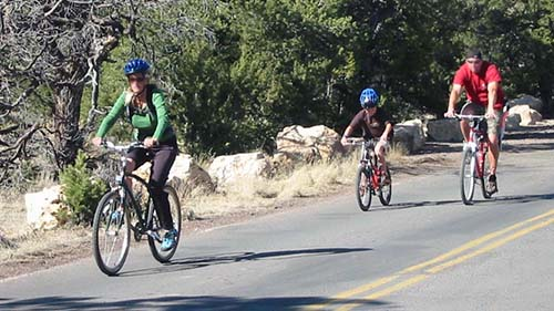 A family of three wearing helmets is bicycling is riding along road.
