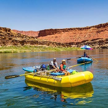 two people wearing life jackets are rowing a yellow inflatable raft on calm river water. a second blue raft is following them.