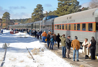 Winter train arrival with passengers on walkway alongside train. Snow on ground.