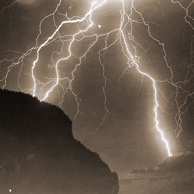 Sepia toned historic photo of multiple lightning strikes. Rim is in silhouette