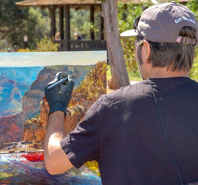 An artist wearing a t-shirt and cap is painting a landscape of canyon peaks and cliffs.