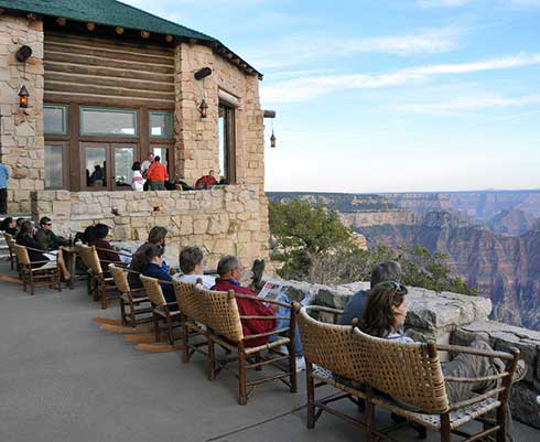 Visitors sitting on the veranda of the North Rim Lodge looking out at Grand Canyon