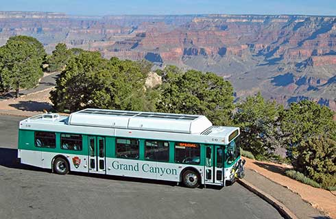 Full length view of Kaibab Route shuttle bus at Yaki Point. Grand Canyon beyond.
