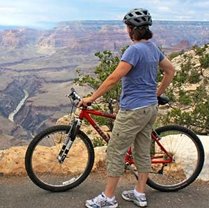 a woman with a red bicycle is standing at the edge of Grand Canyon and looking down at the Colorado River