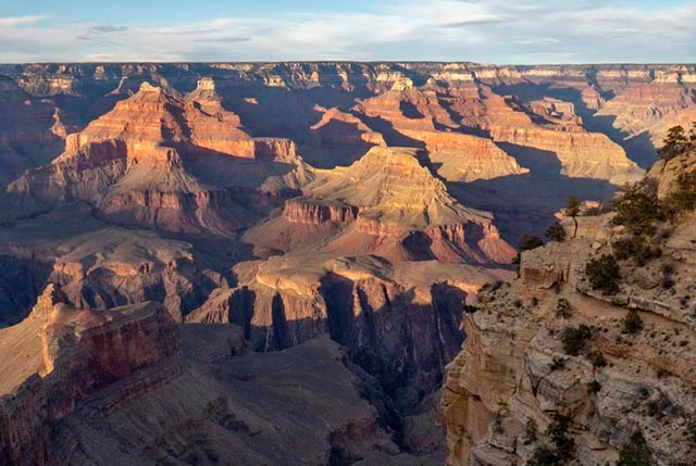 Within a vast canyon landscape, colorful cliffs and peaks are becoming engulfed by evening shadows.