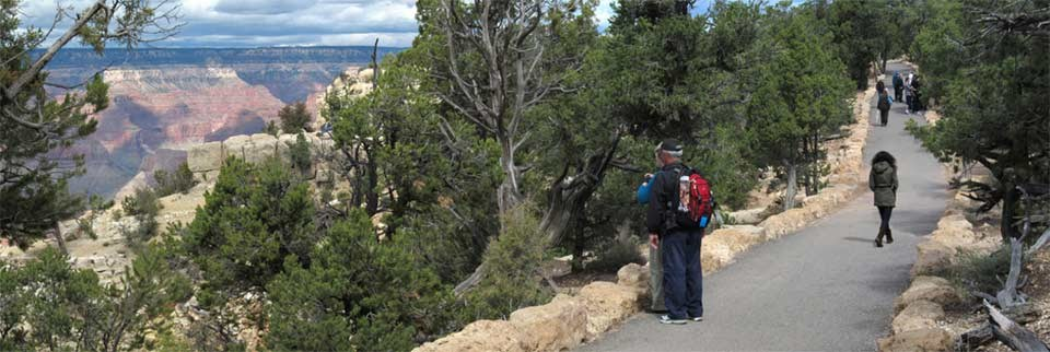Several people walking along the Canyon Rim Trail on the right. Grand Canyon is visible on the left.