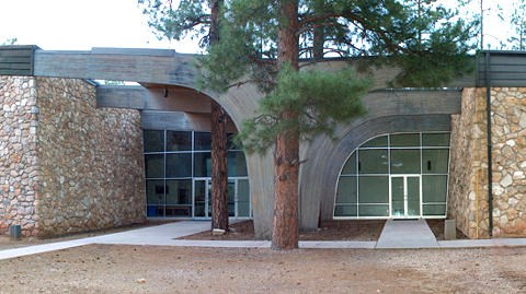 Large two-story building with stone walls and two, large arches that frame entryway walls with glass doors and floor to ceiling windows.