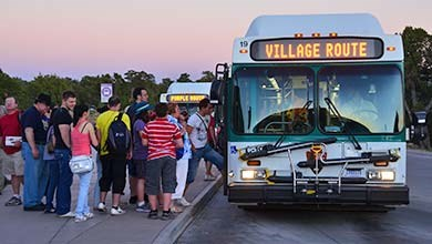visitors boarding the Village Loop Shuttle Bus at dusk.