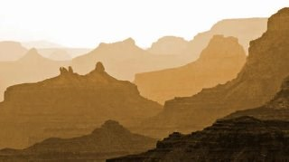 a number of silhouettes of buttes and cliffs receding into the distance and bathed in orange light