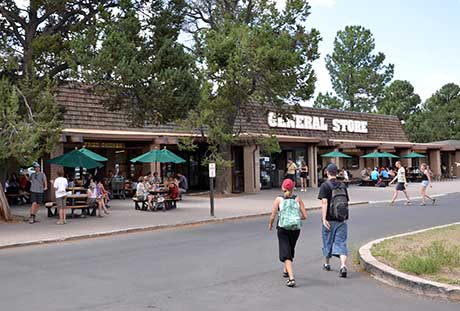 Two people walking across street towards general store. outside picnic tables with green umbrellas