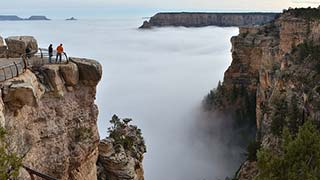 Two people looking out across a cloud inversion that is filling Grand Canyon